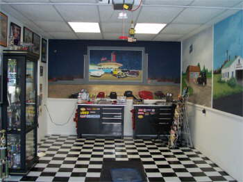 Spencer's Showroom for his 1941 Ford Pickup. We had murals paintted on the wall, a lot about our life. As you drive in the room you face a drive-in movie. American Graffiti is playing and all the cars from the movie are painted parked at Mel's Diner. The