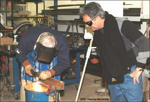 Tony looks on as Ward demonstrates the proper cutting technique.