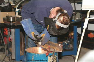 Steve Saunders takes a turn with the plasma cutter.
